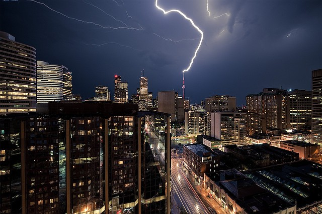 A big city skyline at night hammered with huge lightning. It looks scary and impressive at the same time.