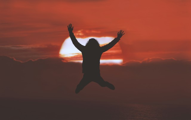 Man jumping in front of a dark red sunset. Spectacular shot!