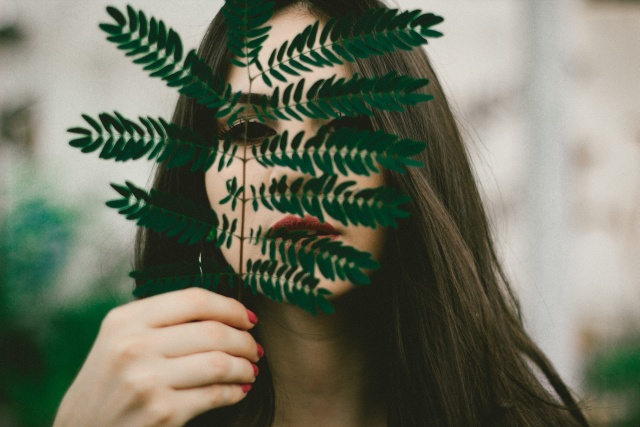 Beautiful brunette woman hiding behind a green branch with lots of leafs she holds in her hand