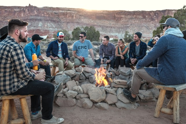 A group of ten friends sitting around a campfire somewhere in the mountains. It's probably Arizona or Nevada. Two women are among the group. They are talking and laughing.
