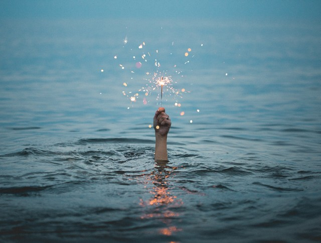 A hand showing from under water in the sea holds a burning sparkler.
