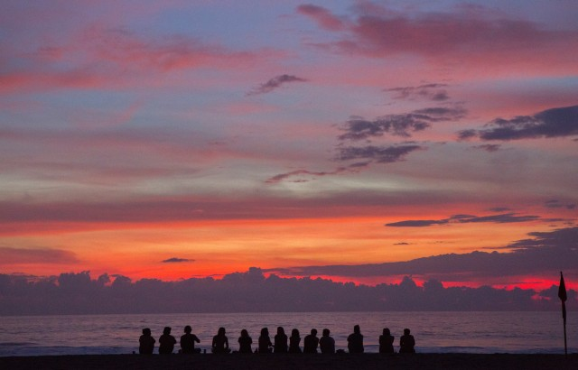 A group of friends sitting on the beach besides each other and watching an epic red and orange and violet sunset somewhere in Mexico.