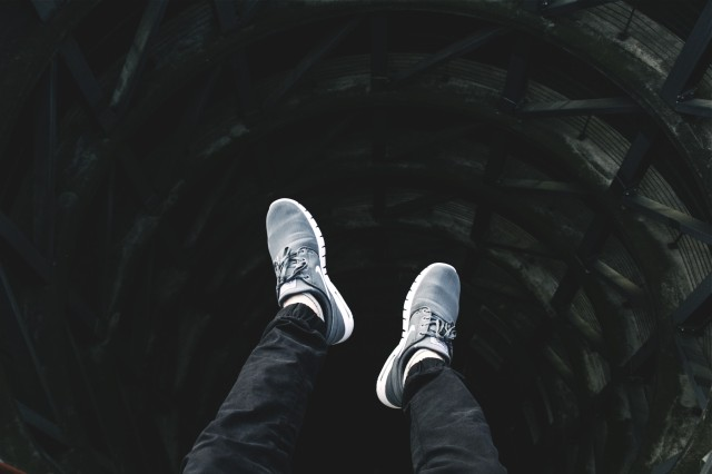 Man sitting above a black hole built in the ground. We only see his knees, feet and sneakers dangling above the abyss.