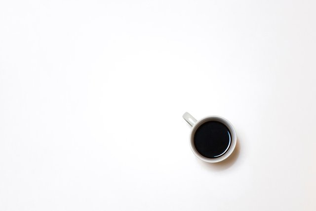 White cup of coffee on a white table. Th ecup is in the bottom right corner.
