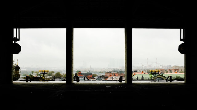 A dark room with three windows. You can look out at a town with a bright albeit grey sky. It's quite a contrast.