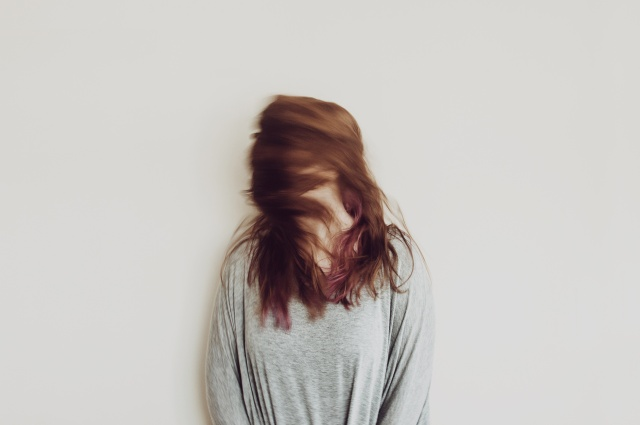 A woman shaking her head so that her long hair covers her face. Looks a bit crazy.