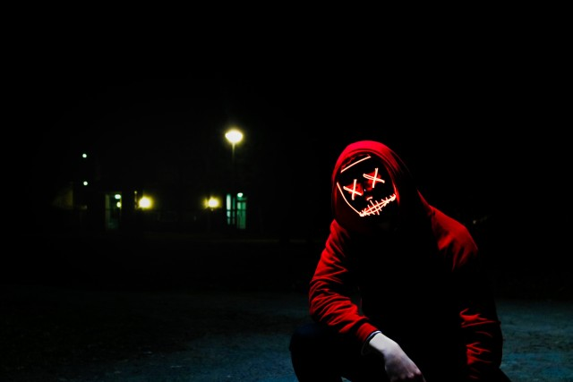 Creepy looking guy wearing a red hoody squats in the dark. His eyes are ligh graffiti crosses, his mouth a light line. It seems there is a car in the background - we see the headlights.