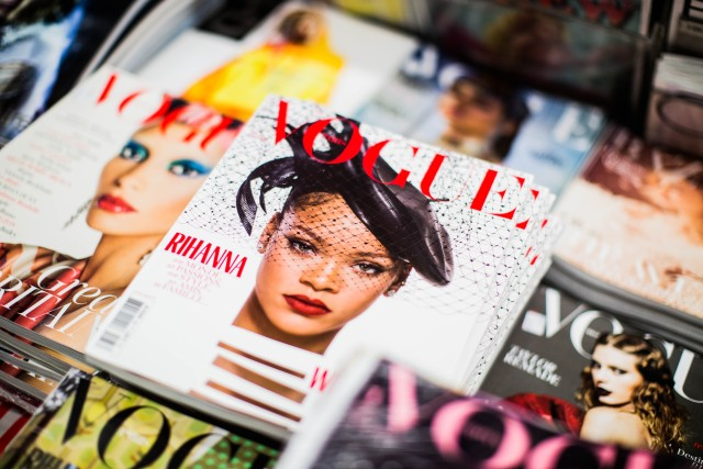 Lots of differnet vogue magazines. The most visible cover features Rihanna on its cover wearinga veil and a hat like in the roaring twenties.