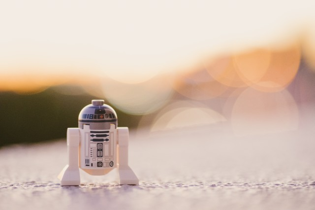 "Star Wars robot R2D"" is moving alone on a sandy path which looks like part of a desert planet, maybe Tatooine."