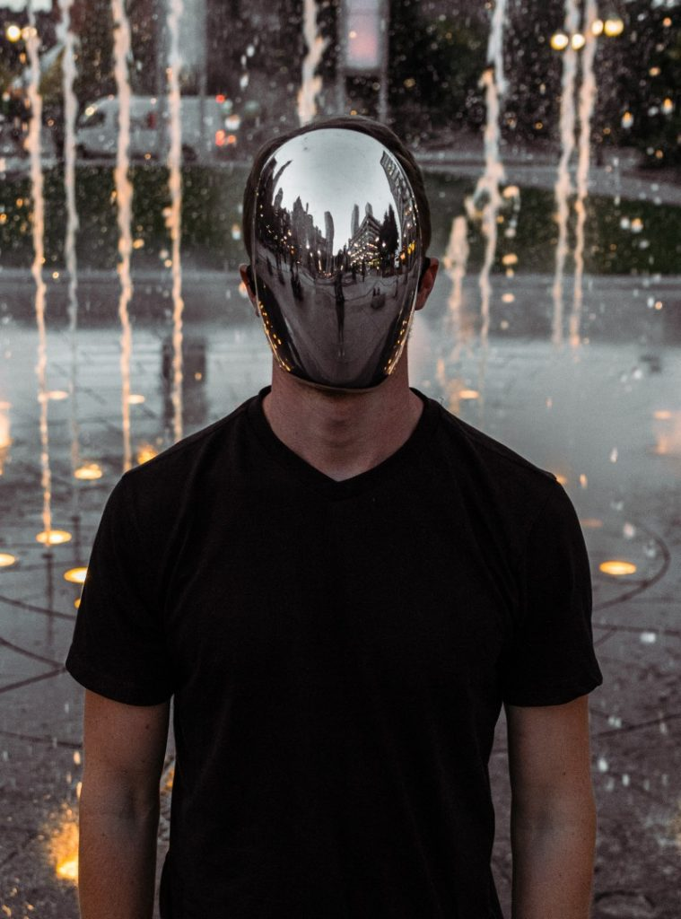 A man wearing a mirror mask is standing in front of a water fountain illuminated by light in the floor.