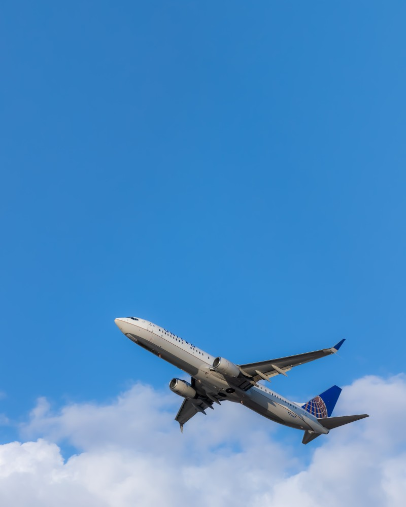 United Airlines plane taking off in front of blue sky.