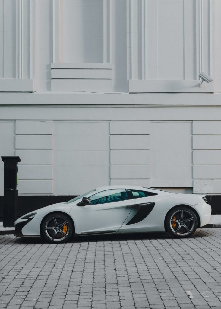 White McLaren 650s in front of white building