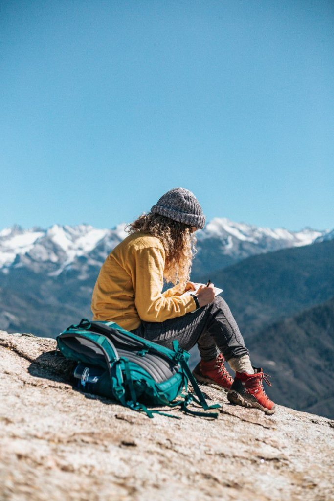 Woman writing in the snowy mountains on a beautiful day.