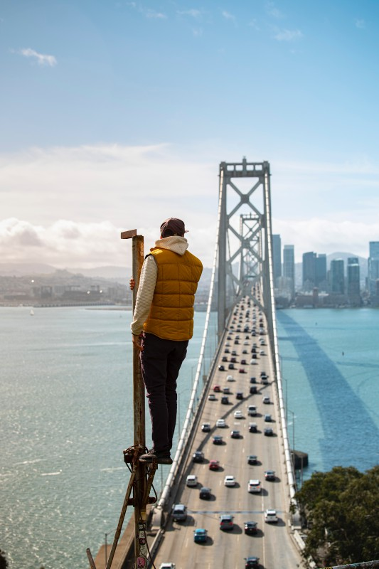 Man watching the Golden Gate Bridge in San Francisco from an elevated structure.