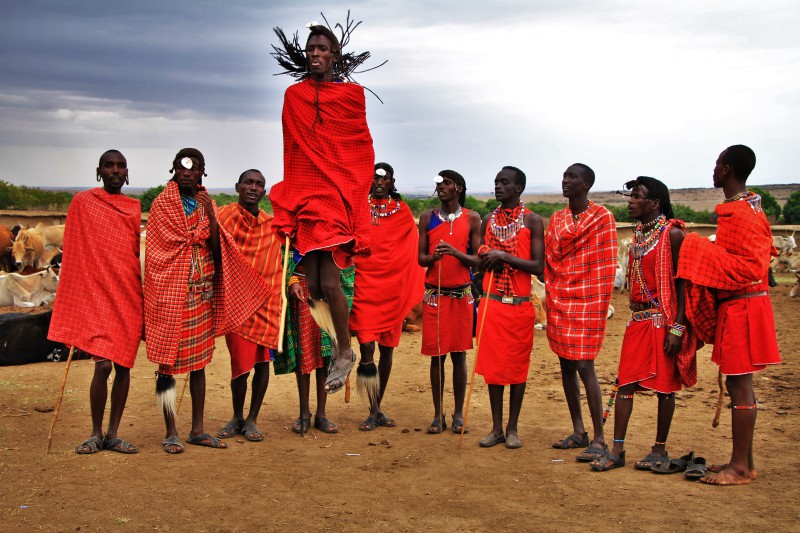 African tribe dressed in colorful - mostly red- robes and one man jumping.